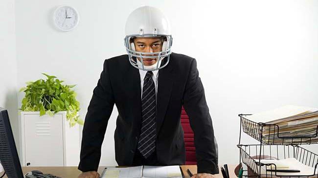 Businessman wearing american football helmet